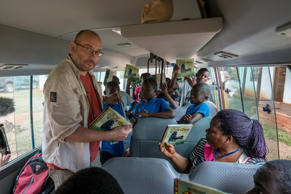 Miroslav Bobek, Prague Zoo's Director, hands out Gorilla Tales to the Wandering Bus participants. Over the last ten years more than 30,000 copies of this book have been printed and distributed among children in Central Africa and it is a big hit among both the schoolchildren and their teachers. The book means the children get to see the gorillas in a new light and not just as meat on a plate. They also gain a whole new experience from a well-made book.