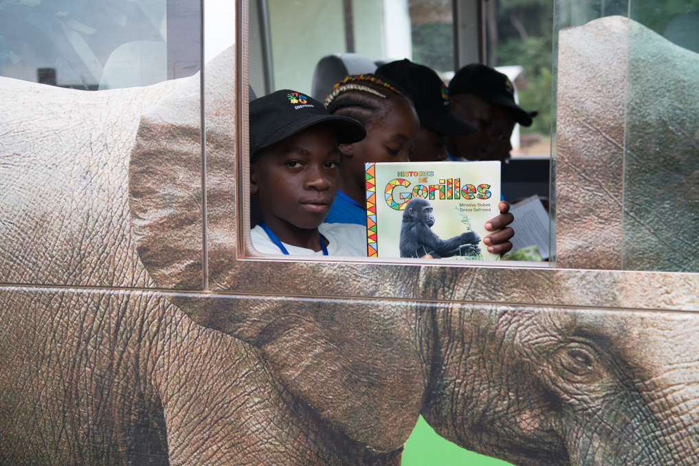 "Through an open window of the Wandering Bus Miguel Djibril Soma shows his copy of the storybook, whose main heroes are Richard and other members of the gorilla family in Prague Zoo. The last six thousand copies for their Cameroonian peers were paid for by Czech children from Centipede – the ""Movement on Own Feet""."